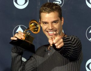 "LOS ANGELES, UNITED STATES: Puerto Rican singer Ricky Martin poses with his Grammy Award for Best Latin Pop Performance for the album ""Vuelve"" at the Shrine Auditorium in Los Angeles, 24 February. (Electronic Image) AFP PHOTO Vince BUCCI (Photo credit should read Vince Bucci/AFP/Getty Images)"
